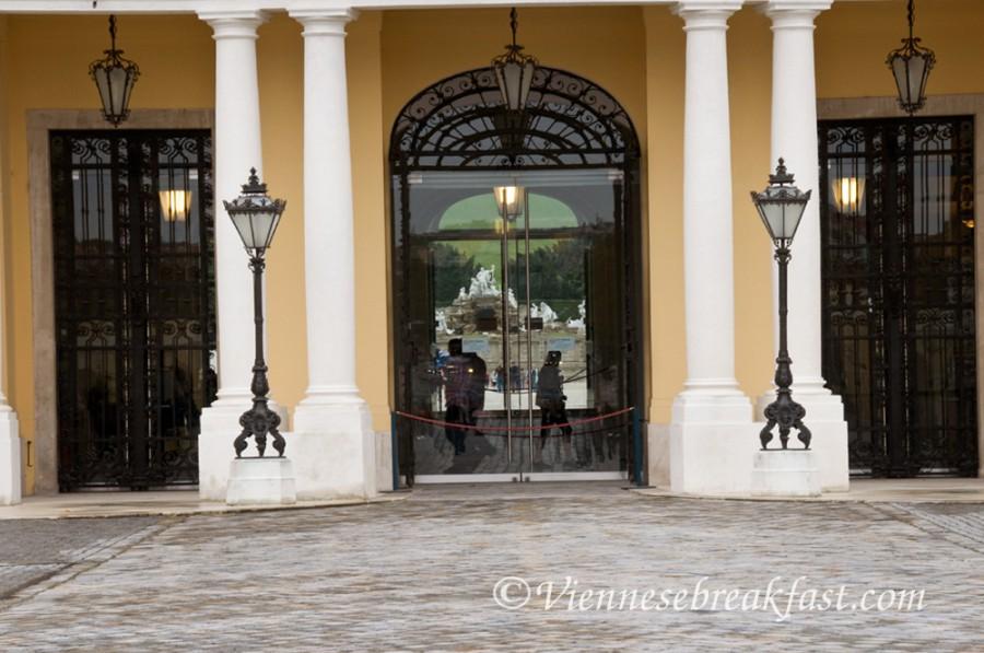 Patrząc przez przeszklone drzwi Pałacu zobaczycie Fontannę Neptuna